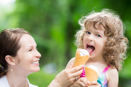 Happy child eating ice cream outdoors in summer park photo