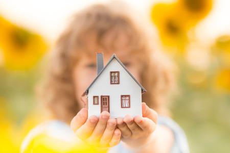 Huis in de hand tegen de lente groene achtergrond. Onroerend goed begrip Stockfoto