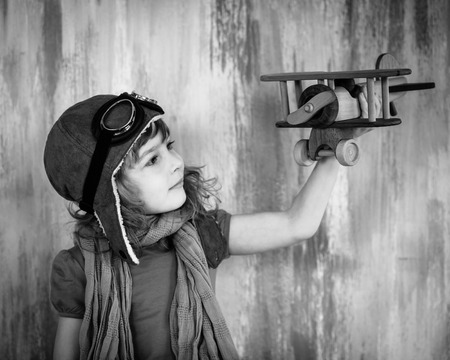 Happy kid playing with toy wooden airplane indoors. Black and white photo photo