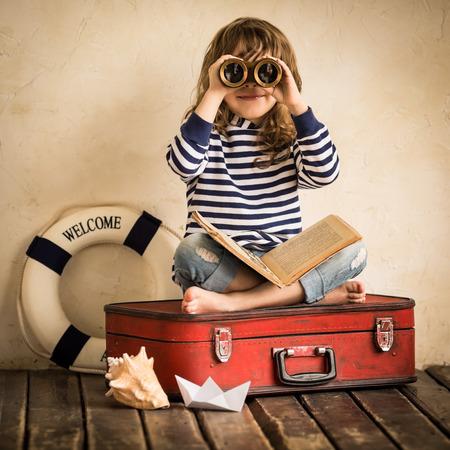 aventura: Cabrito feliz que juega con el juguete del barco de vela en el interior. Viajes y aventura concepto