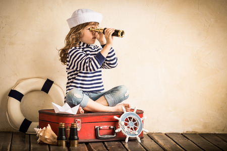 old toys: Happy kid playing with toy sailing boat indoors. Travel and adventure concept Stock Photo