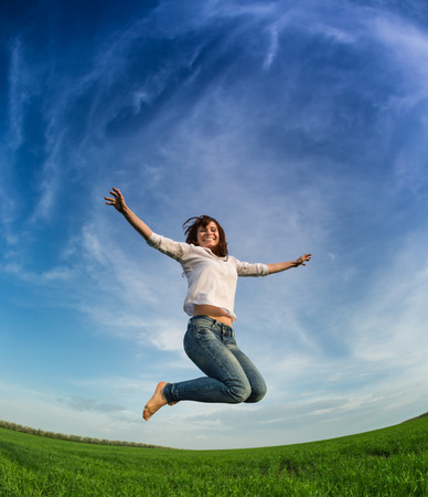 Happy woman jumping in green field against blue sky. Summer vacation concept photo