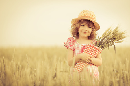 Happy child holding wheat in summer field photo