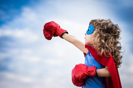 sen: Superhero dítě proti letní obloze na pozadí. Dívka výkon a feminismus koncept