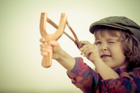 Kid holding slingshot in hands against summer sky background. Retro style photo