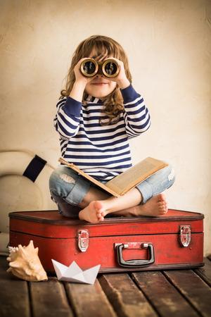 Grappige jong geitje het spelen met speelgoed zeilboot binnenshuis. Reizen en avontuur concept