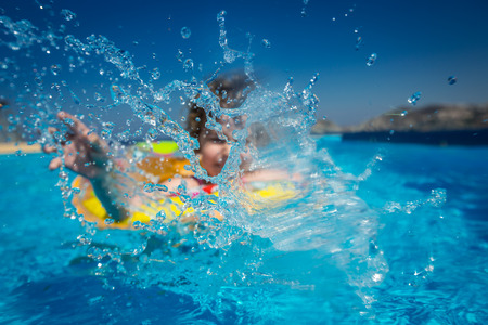 Happy child playing in swimming pool. Summer vacations concept. Focus on splash photo