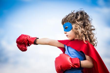 劇的な青い空を背景のスーパー ヒーローの子供