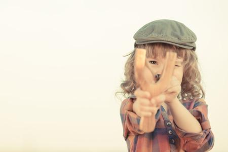 Child holding slingshot in hands against summer sky background