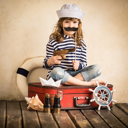 Happy kid pirate playing with toy sailing boat indoors Stock Photo