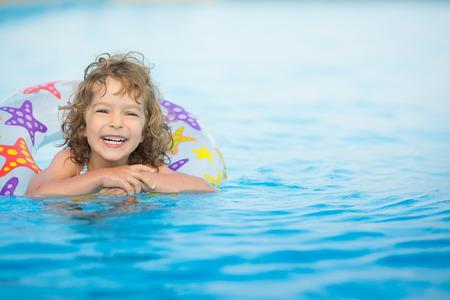 スイミング プールで遊んで幸せな子供 写真素材