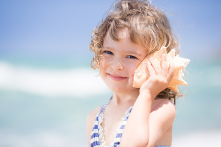 Happy child with sea shell at the beach Banco de Imagens