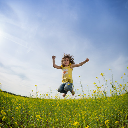 Happy family jumping in green field against blue sky photo