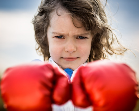 feminism: Kid wearing red boxing gloves. Girl power and feminism concept
