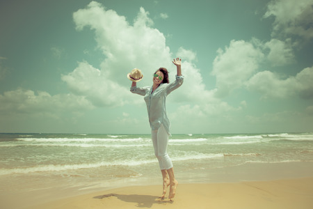 Happy woman jumping at the beach against blue sky background. Summer vacations concept photo