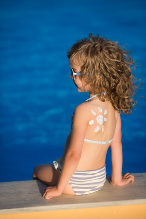 Sunscreen lotion sun drawing on children's back. Summer vacations concept photo