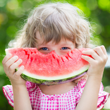 watermelon slice: Funny kid eating watermelon outdoors in summer park