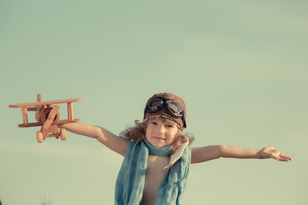 Happy kid playing with toy airplane against summer sky background photo