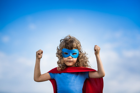 kids exercise: Superhero child against blue sky background