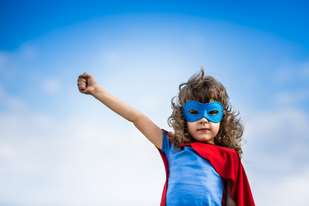 Superhero child against blue sky background photo