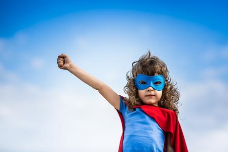 Superhero kind tegen de blauwe hemel achtergrond Stockfoto