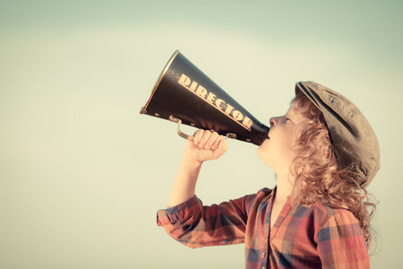 Kid shouting through vintage megaphone. Communication concept. Blue sky background as copy space for your text photo