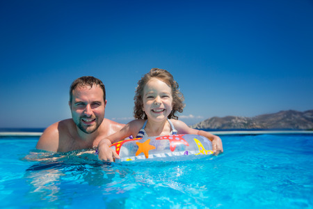 Happy child with father playing in swimming pool. Summer vacations concept photo