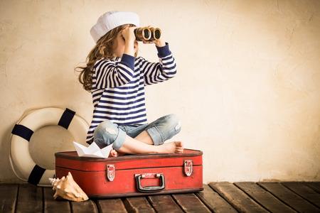 Cabrito feliz que juega con el juguete del barco de vela en el interior. Viajes y aventura concepto