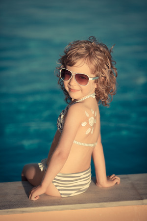 Sunscreen lotion sun drawing on childrens back. Summer vacations concept photo