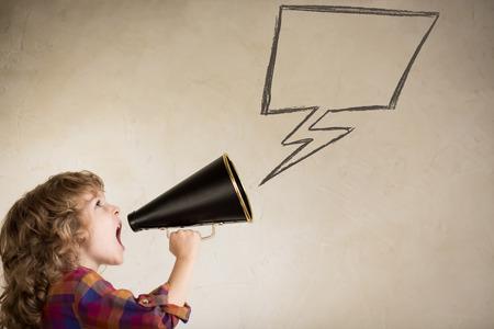 megafono: Kid gritando por megáfono vintage. Concepto de comunicación. El estilo retro