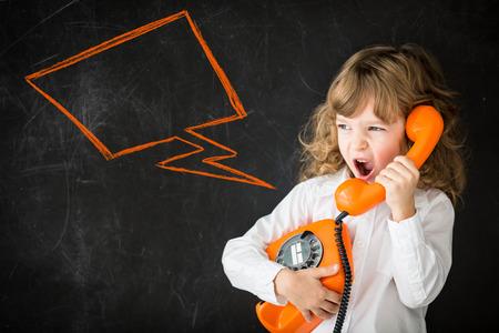 espalda: Kid gritando en teléfono de la vendimia. Concepto de la educación. Copie el espacio para el texto