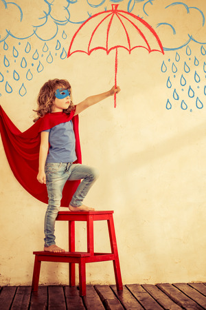Full length portrait of superhero kid against grunge wall background Stok Fotoğraf