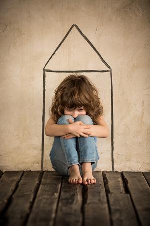 vagabundos: Niño sin hogar triste siiting en el suelo en una habitación oscura Foto de archivo