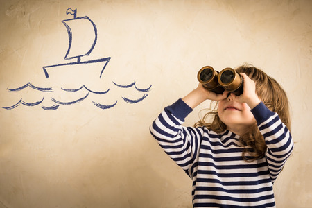 marinero: Niño feliz jugando marinero en el interior. Niño sonriente mira dibujo barco. Viajes y aventura concepto. Vacaciones de verano Foto de archivo