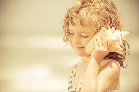 Gelukkig kind luisteren naar zeeschelp op het strand. Zomervakanties begrip