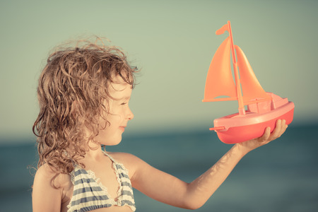 Happy kid playing with toy sailing boat against summer sky background photo