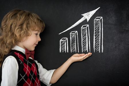 Happy child against blackboard Drawing growth bar graph