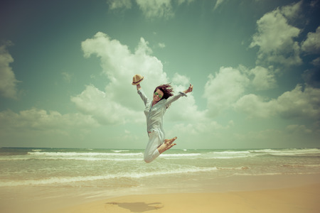barefoot women: Happy woman jumping at the beach