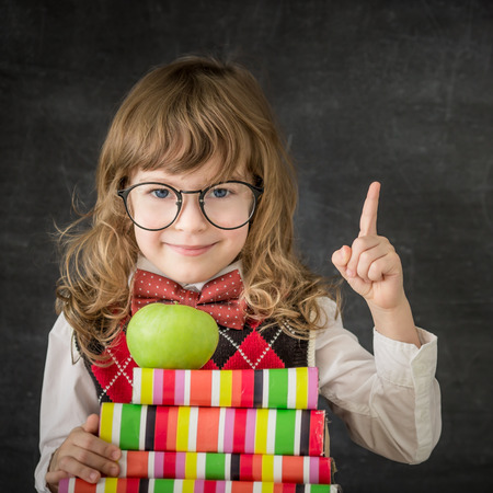 Happy child against blackboard with apple and presents