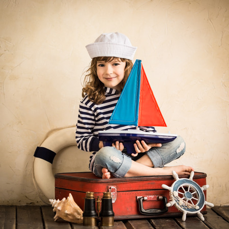 Happy kid playing with toy sailing boat indoors photo