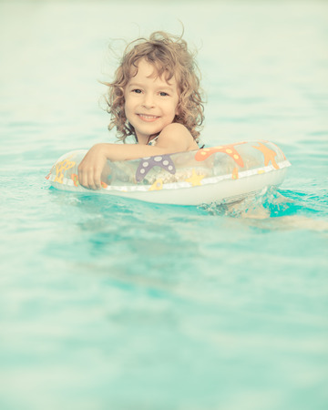 Happy child playing in swimming pool photo