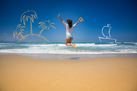 Happy woman jumping at the beach against blue sky and sea background photo