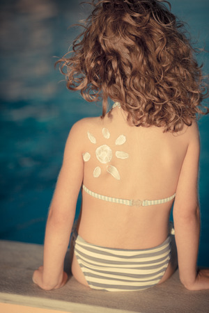Sunscreen lotion sun drawing on little girl back photo