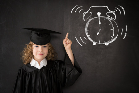 Smart kid in class. Happy child against blackboard. Drawing alarm clock photo