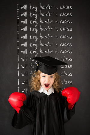Smart kid in class. Funny child against blackboard. Back to school. Education. Knowledge is power concept photo