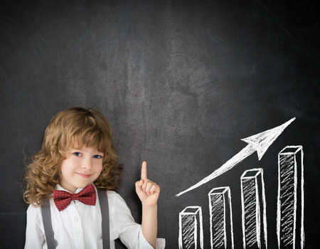 pizarron: Chico inteligente en clase. Niño feliz contra la pizarra. Dibujo gráfico de barras de crecimiento. Concepto de negocio