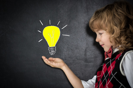 Smart kid in class. Happy child against blackboard. Bright idea business concept photo