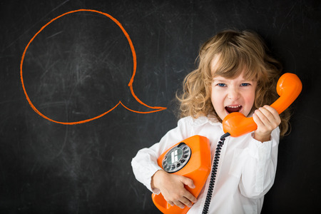 Kid shouting through vintage phone. Business communication concept photo