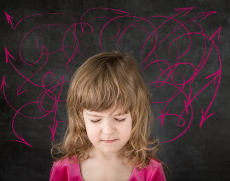 Funny child against blackboard. Smiling kid in class. Drawing arrows. Conception  photo