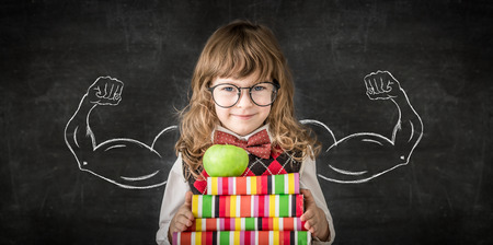 Smart kid in class. Happy child against blackboard. Knowledge is power concept Stock Photo - 28213877